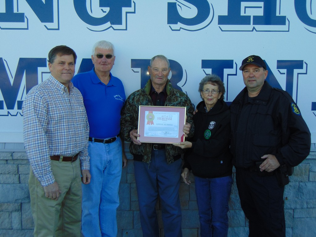 IN RECOGNITION OF A DRAMATIC RESCUE, the US Army Corps Of Engineers presented a plaque to Lonnie Murrell for his efforts in the rescue of passengers from a capsized boat on Truman Lake. Attending the ceremony at Long Shoal Marina were Corps of Engineers Operations Manager James Sandberg, Don Eckers, Lonnie Murrell, Sondra Murrell, and Missouri State Trooper Tim Murrell.