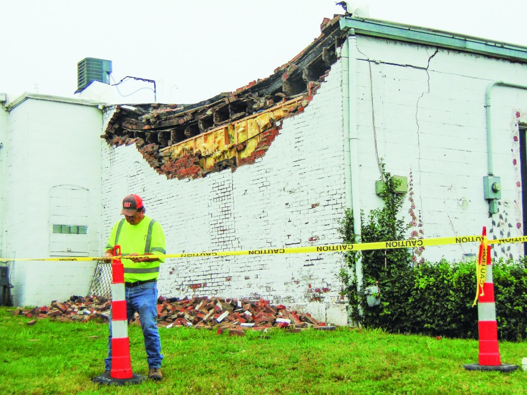 THE LANE BUILDING ON WARSAW'S MAIN Street suffered severe damage during last night's storm. The rear section of the building partially collapsed. Warsaw City worker Buster Young cordoned off the area early Tuesday morning.