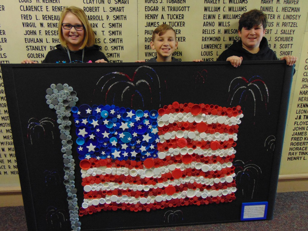 PRIDE AND GRATITUDE is on display at the Benton County Courthouse with a handmade flag to honor veterans. Warsaw R-IX South students Madalyn Arnett, Braydon Henderson and Isaac Henderson helped produce the stunning work.