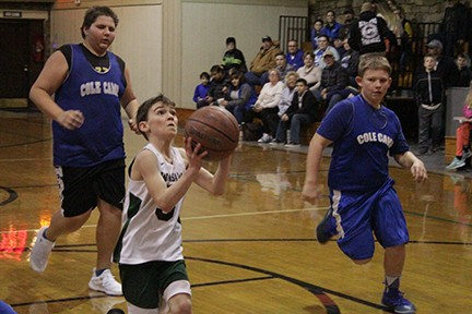 SHANE POYSER DRIVES FOR A BASKET against Cole Camp in the Lions Club Tournament last Week. Cole Camp won 31-9. Despite weather conditions, the tournament was a huge success.
