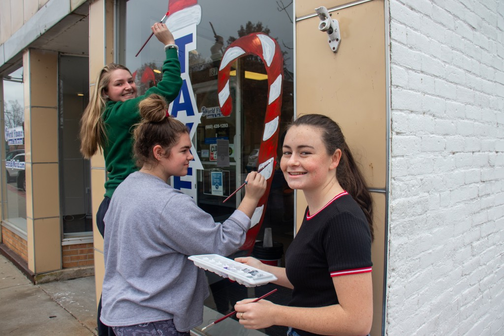 SHOWCASING THEIR ARTISTIC SKILLS, WHS juniors Brooke Spry, Taylor Spry and Gabrielle Porter painted downtown Warsaw store fronts with holiday themes to raise money for prom.