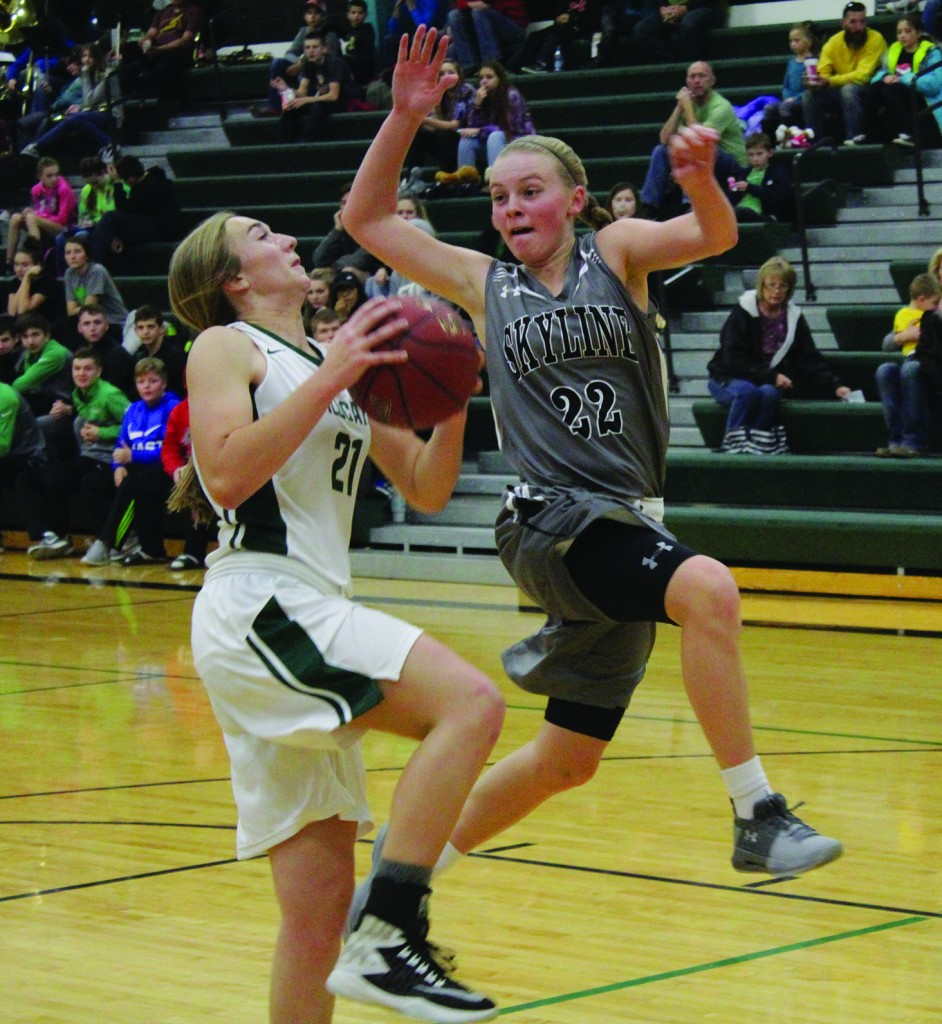 Aubrie Mcroberts Drives To The Basket while being guarded by Skyline's Autumn Garrett. The defending Class 1 State Champions ,the Skyline Lady Tigers defeated Warsaw 65-31 last Friday night at the WHS gym.