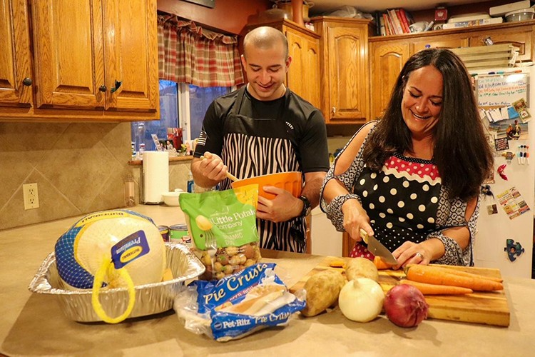 THANKSGIVING PLANS HAVE PIVOTED for many families due to COVID-19.  Heather Montez and her son  Joe prepped food for a smaller gathering this year.