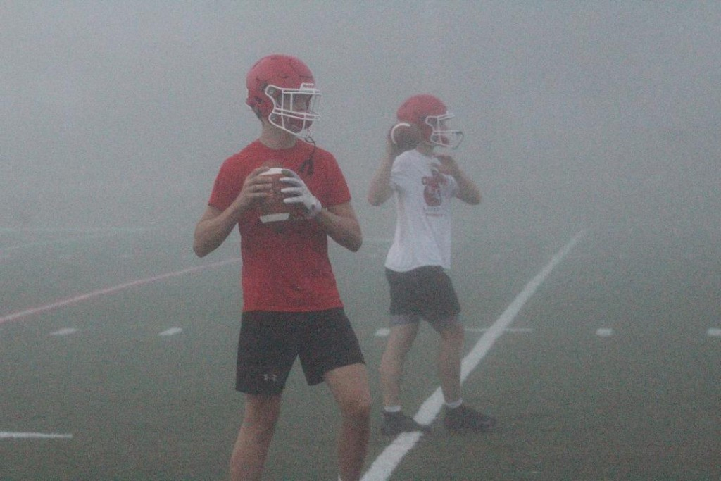 LINCOLN QB KYLE ECKHOFF PRACTICES in the fog on Wednesday morning. Things went on as normal as they broke up in groups. However, they had trouble seeing the scoreboard to keep track of the allotted time for each drill ran.