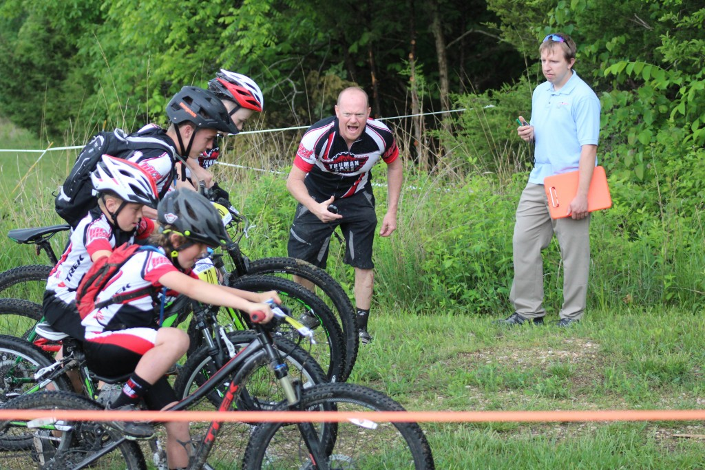 GET READY, SET,  GO! Mac Vorce starts the 14U racers last Saturday at the Truman Lake Mountain Bike Park  in Warsaw for the Down N' Dirty Missouri Championship Mountain Bike Race. Looking on is USA Cycle Official Andy Schuette. Pictured are front row racers Jett Fluty (#74), (Caden Casteel (#70), Hunter Dority (#59) and Joe Vorce (#69).