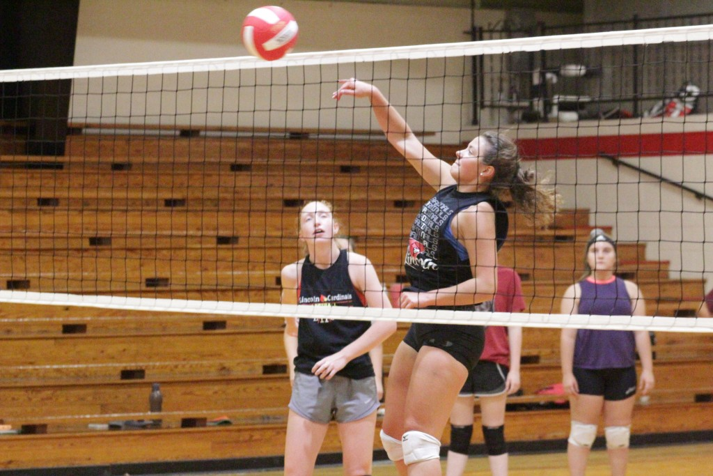 LINCOLN'S CALLIE SPUNAUGLE punishes the ball over the net during  volleyball open gym practice at Lincoln last week. Spunaugle will be one of Lincoln's big hitters this season.
