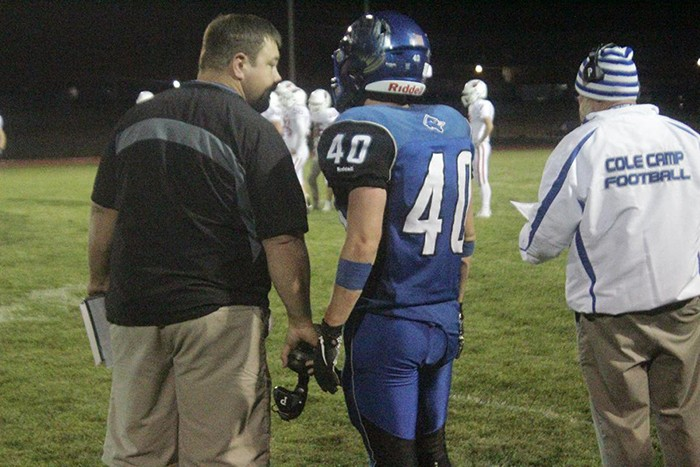 ASSISTANT COACH NATE STEENBURGEN talks to Jamison Farrar as Head Coach Kevin Shearer plots their next play. Cole Camp won 14-13 with fourth quarter heroics.