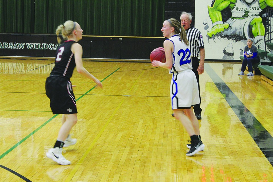 KEILI TOUGH GUARDS Cole Camp's Tori Harding (#22) in Monday night action in the Warsaw tournament. El Dorado pulled off the upset with a 55-45 victory in the first round.