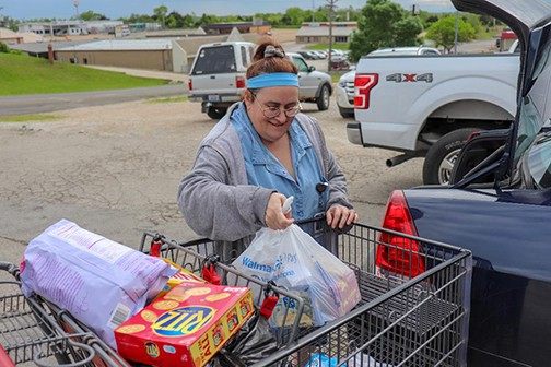 "MAKING ENDS MEET, Terri Forsee shopped at the Benton County Food Pantry in Warsaw on Monday. Forsee told the Enterprise, ""I'm a working Mom with two children. There are times during the month that it would be impossible without the pantry. I'm really thankful it's here."""