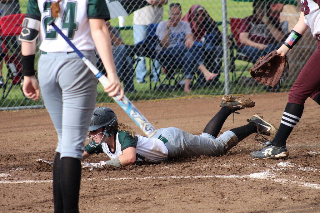 KYLEE FAJEN BELLY FLOPS INTO A MUD HOLE at home plate in the second inning. Fajen would pitch the Lady Cats to a 10-0 victory over Weaubleau on Wednesday night in a make-up game from the week before.