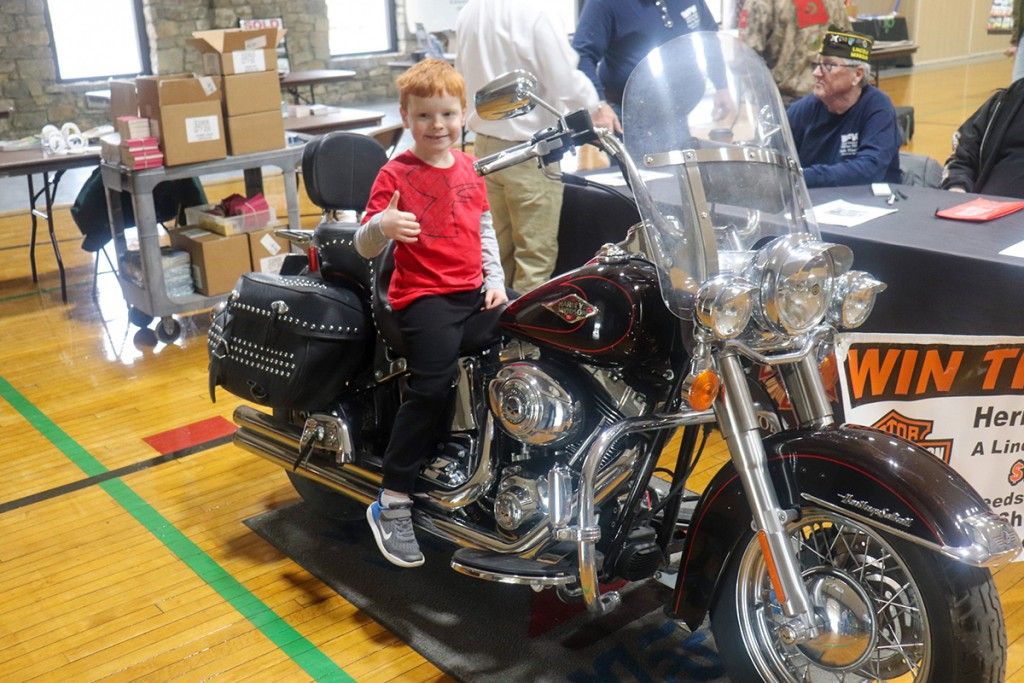 DREAMING OF WARM WEATHER and the open road, Eli Slavens climbed aboard a Harley Davidson motorcycle during Saturday's Lake Life Hunting & Fishing Show. The event was hosted by the Warsaw Area Chamber of Commerce at the Warsaw Community Building.