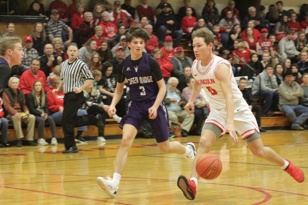 LINCOLN'S BO KROENKE DRIVES DOWN the court against Green Ridge on Friday night. Lincoln won their Homecoming contest, 63-52. Kroenke led the way with 28 points.