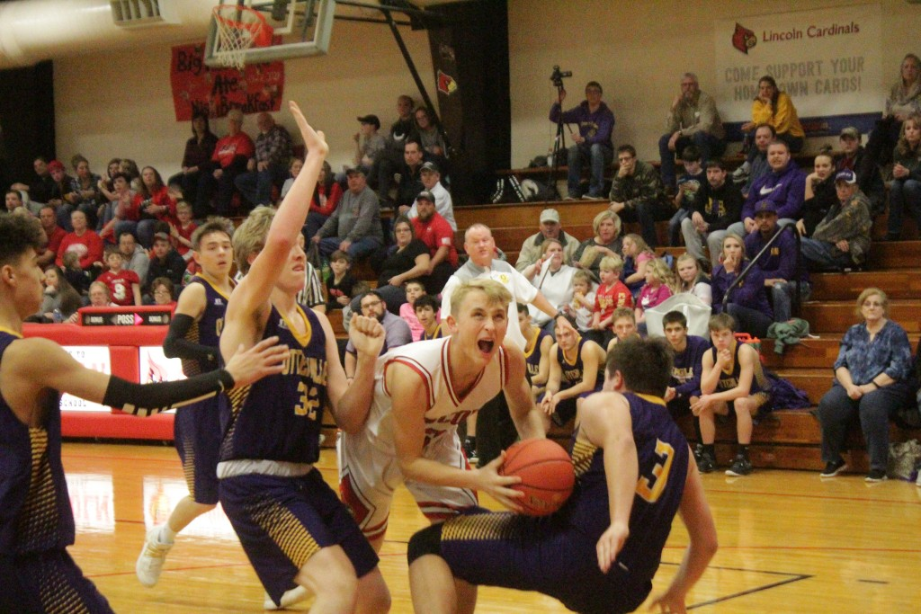 LINCOLN'S LEVI BETTS CRASHES into two Otterville defenders on his way to the basket last Friday night In Lincoln.