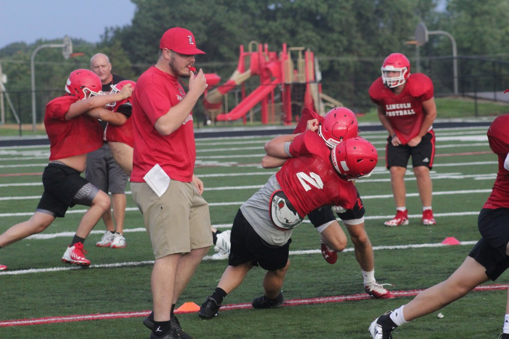 CONNOR SPUNAUGLE watches the Lincoln football  players battle it out at football camp last week. Spunaugle, former all state baseball and all district football player,  is one of the new assistant coaches at Lincoln.