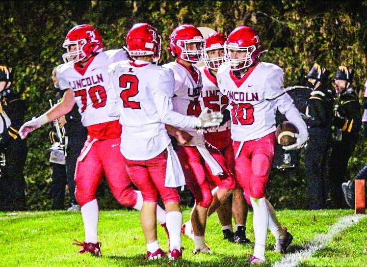 CADEN SMALLWOOD (#2), Ely Tolliver (#70) and Emidio Linares (#52) among others, congradulate Connor Lynde (#10) on his second quarter touchdown run. Lincoln won 14-7 over Wellington - Napoleon and moved to 4-4 on the season.