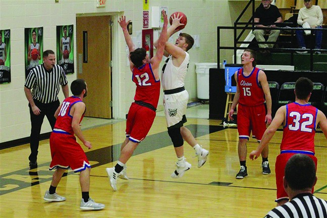 LANE BATES SHOOTS OVER a Clinton defender in the first half of Monday night's battle at WHS. Clinton beat Warsaw 70-60 for their second win of the season over the Wildcats.