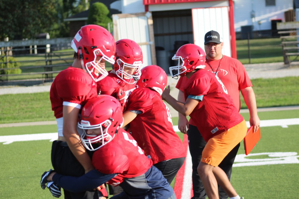 NEW LINCOLN HEAD COACH KEVIN LAFAVOR watches as his players practice tackling last week during their week long evening football camp. Some 30 kids showed up to camp and their performance and attitude on the field gave the Lincoln coaching staff several reasons to be optimistic about the coming season.