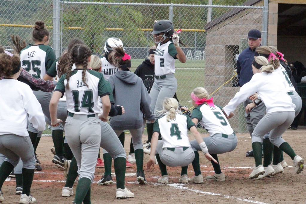 WARSAW'S KYA SCHEPKER IS GREETED by her teammates while she leaps up into the air as she approaches home plate after hitting a 200 ft., two run home run to left center field. Warsaw beat Sedalia Smith Cotton 10-0 to move to 20-3 on the season.