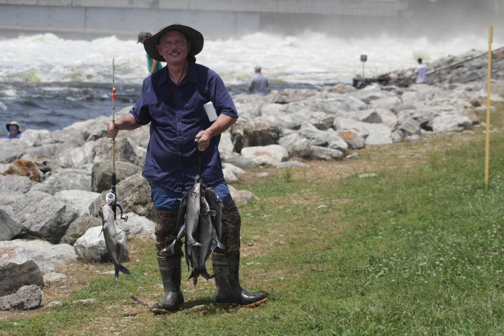 THE FISHERMEN ARE REAPING THE REWARDS of the high water. With the water raging in the background, Lloyd Brewington shows off a mess of pan size catfish he caught below the Dam on Saturday afternoon. Catfish up to 50-60 plus pounds are being caught at night on a pretty regular basis.