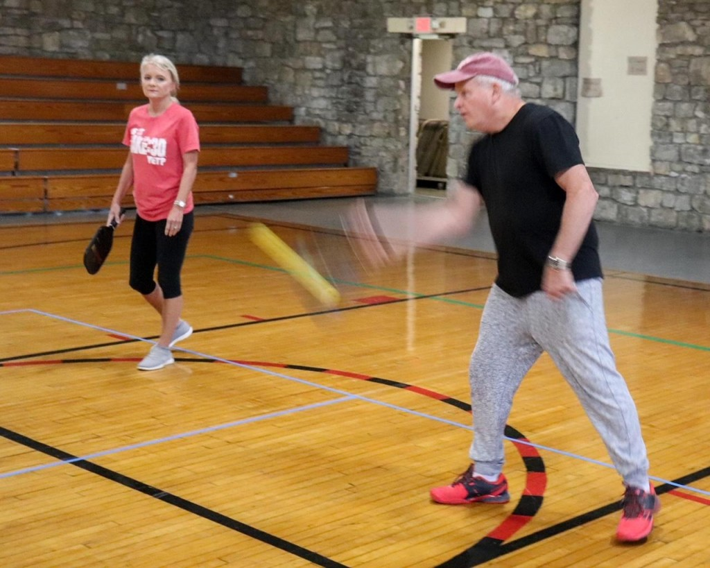 A NEW GAME IN TOWN,  the sport of pickleball is on the rise around the country and in Benton County. Donna and Mike Guy participate in regular games at the Warsaw Community Building.