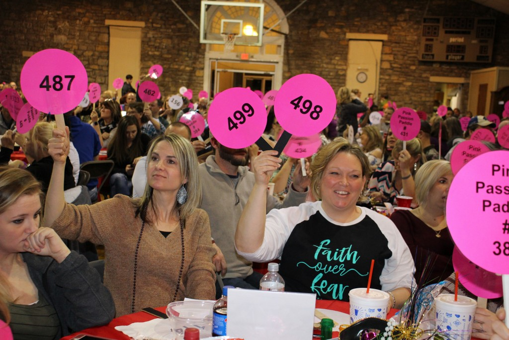 PADDLES PARADED IN THE AIR during Saturday's Quarter Mania at the Warsaw Community Building. Participating in the jam packed event were Julie Bunch and Christina Redwing.