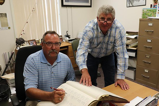 ANTICIPATING THE START OF CONSTRUCTION on the new Benton County Jail, the county will make lease certificates of appreciation available to investors.  County Treasurer Rick Renno and County Commissioner Steve Daleske told the Enterprise they're proud of the strong vote of confidence the county received on the issue from the public.  Incidentally, the certificates will be recorded on a large ledger similar to the one Treasurer Renno and Commssioner Daleske were reviewing when the above photograph was taken.