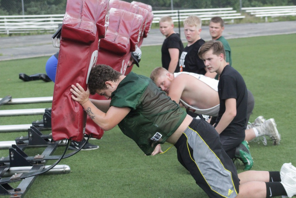 SENIOR LINEMAN TRISTAN REYNOLDS demonstrates how to push the sled during summer workouts at WHS while  other players look on. Reynolds and fellow Senior Lane Bates are being called upon to rebuild the line that was weaken by graduation. The offensive and defensive lines could actually be more athletic this season according to Head Coach Ryan Boyer.