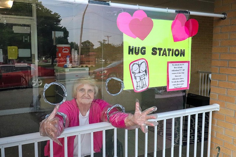 VISITING A LOVED ONE with restrictions is the new normal at Good Samaritan Care Center in Cole Camp. Nancy Paxton stretched her arms out to greet a friend. The facility has erected a plexiglass screen to keep residents and visitors safe amid Covid-19.
